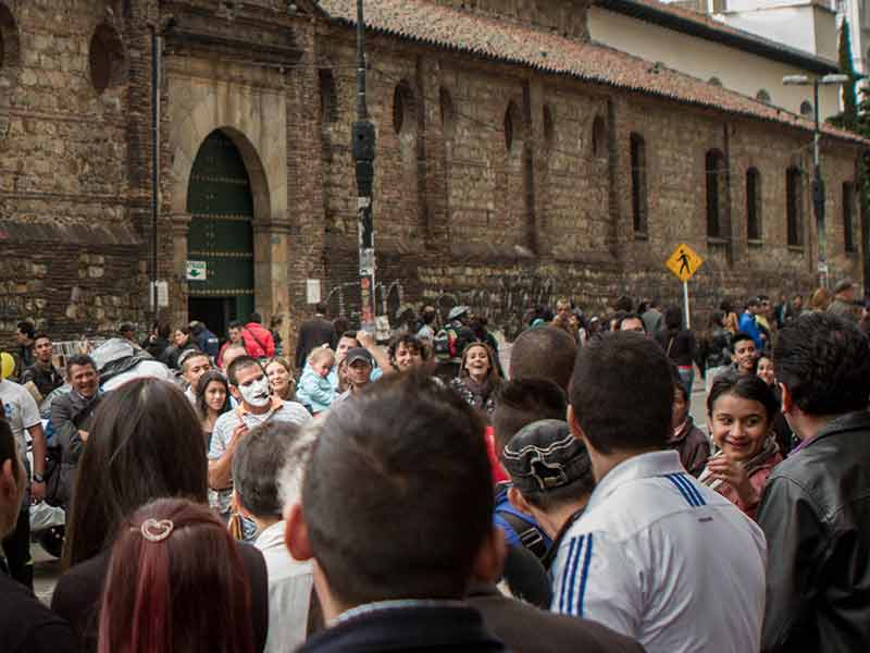 Crowd watches street performers on the streets just outside some of the oldest churches in Bogota.