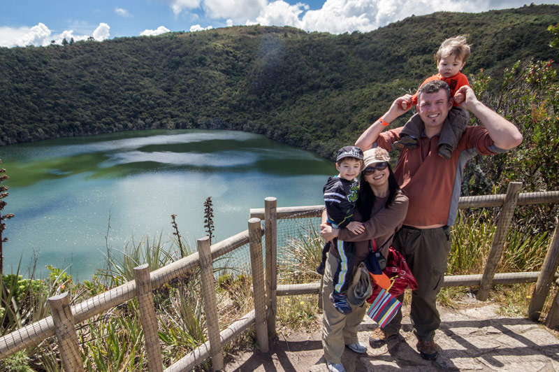 A young family smiles while standing on an overlook over a crater lake surrounded by jungle as they search for the lost city of gold in Guatavita Colombia with kids