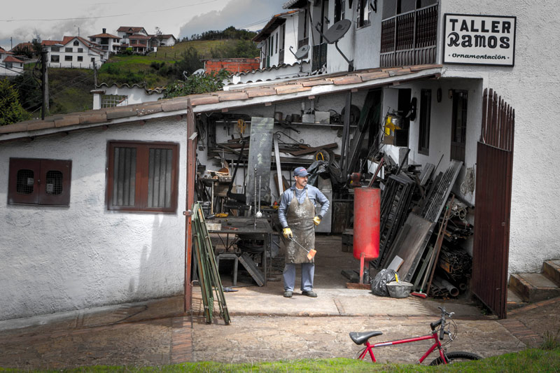 A shop worker looks out from a garage attached to his house - Legend of El Dorado in Colombia