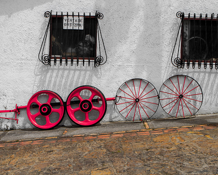 Old colourful tire rims lean up agains a white adobe style wall - Legend of El Dorado in Colombia
