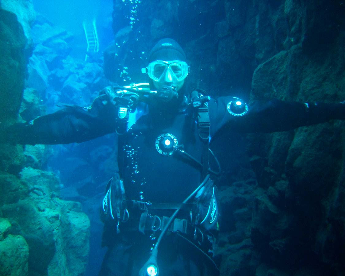 SCUBA diver touches the walls of the Silfra Fissure Iceland