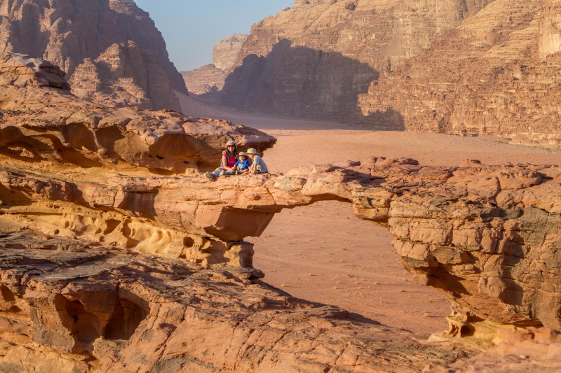 A woman and two young boys watch the sunset from a rock arch in the Wadi Rum desert during Wadi Rum Jeep Tours