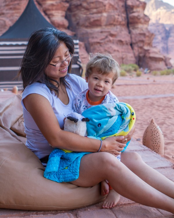 Woman and toddler snuggle in front of a Wadi Rum desert camp at the Wadi Rum overnight luxury camp