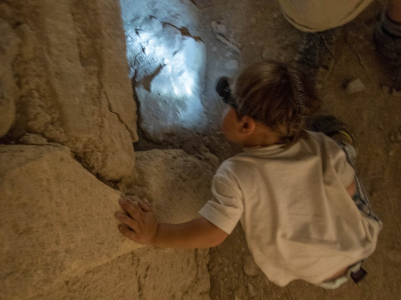 Toddler with headlamp looking in a hole in a tunnel