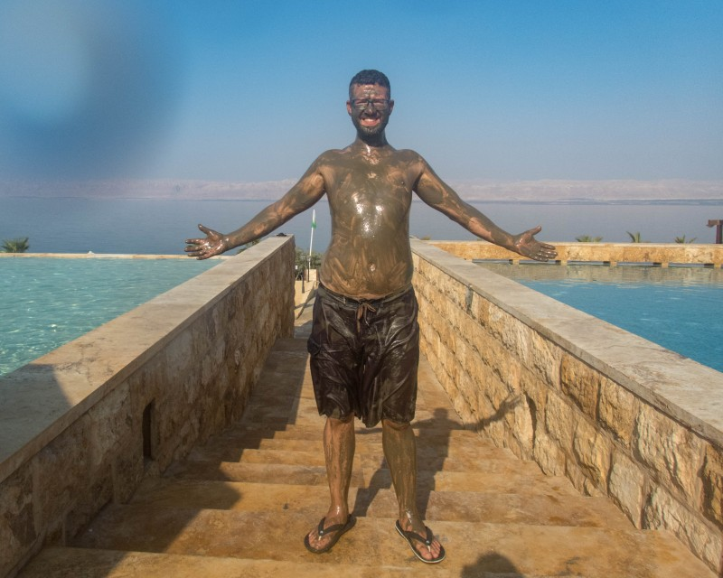 Kevin shows off his muddy body in front of the Dead Sea