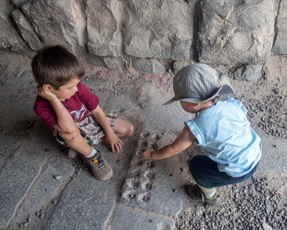 Two boys play a board game built into the floor of Azrak Castle in Jordan