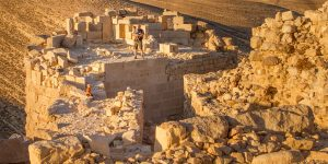 A man and two young boys climb on the top of a crumbling castle in Jordan