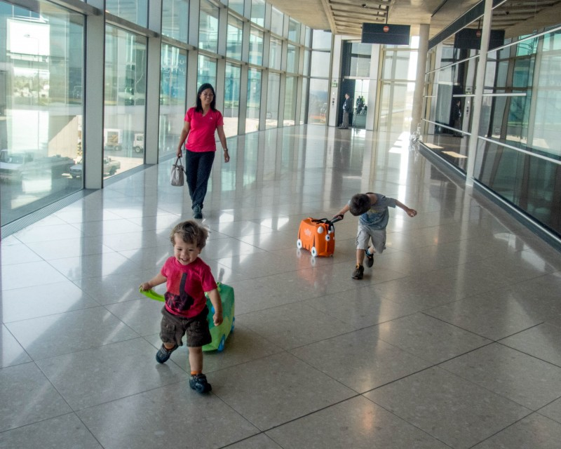 A family runs through an airpot carrying luggage for children
