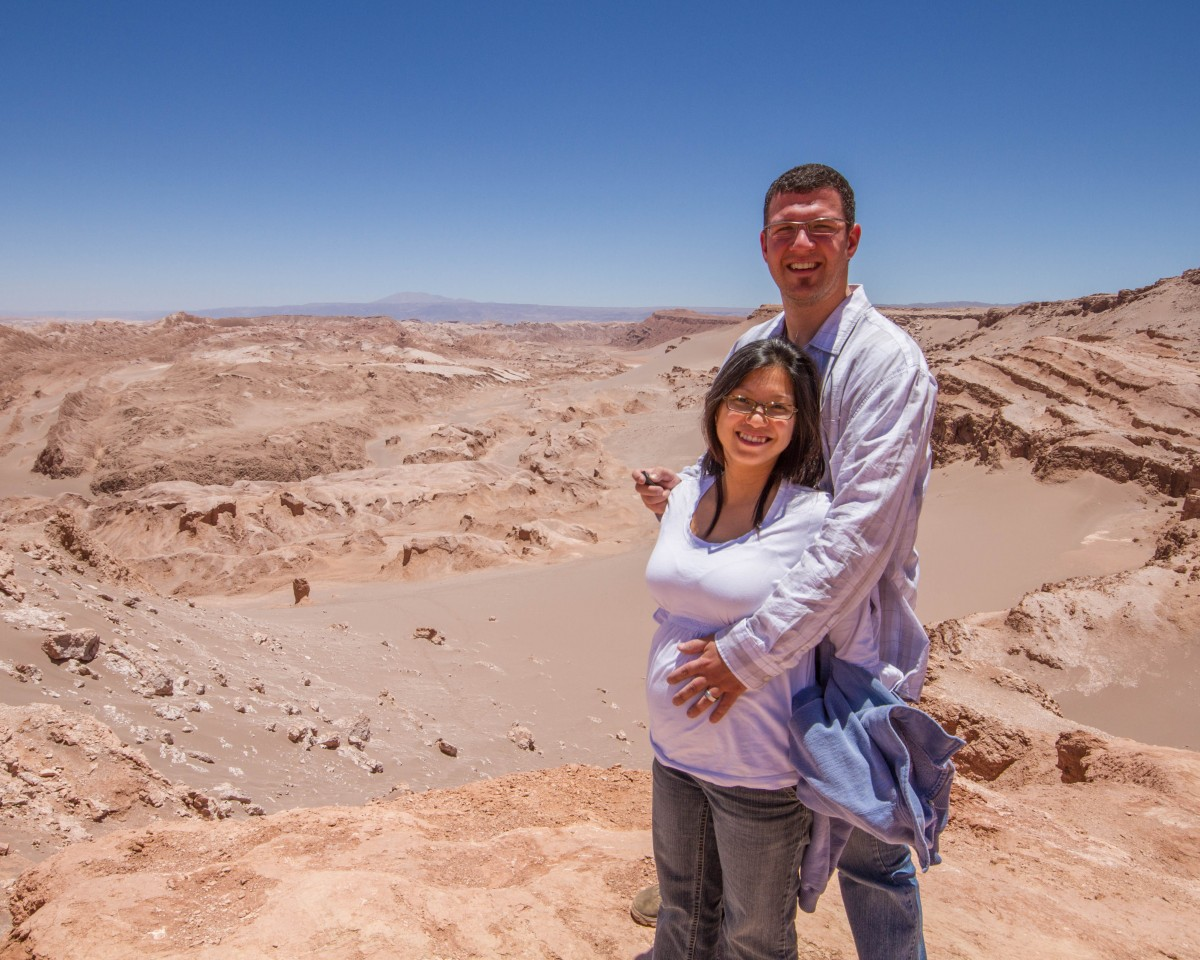 Man and pregnant wife pose for a photo at the Valley of the Dead in Chile