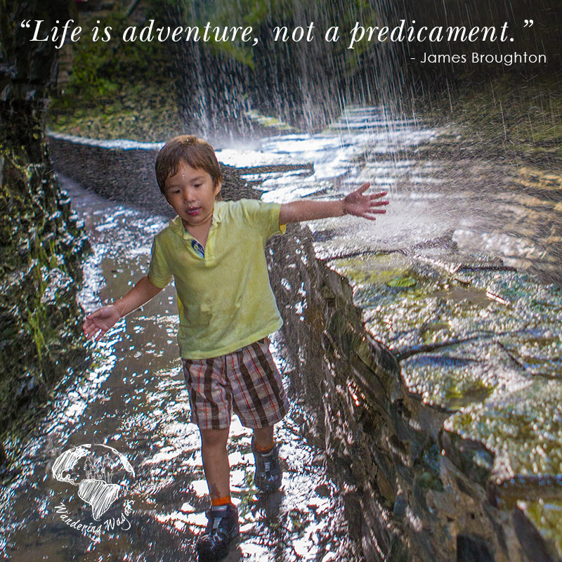 Young boy smiling while walking under a waterfall with his arms raised - Inspirational Quotes
