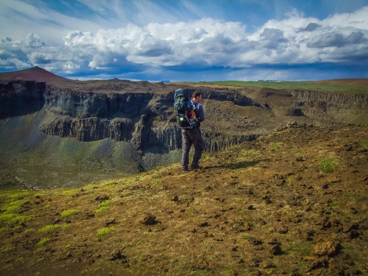 Man carrying child carrier along a steep ridge - Deuter Kid Comfort III