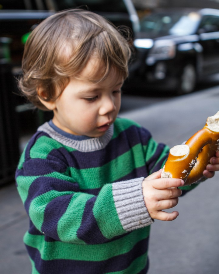 A toddler pulls apart a soft pretzel on the streets of New York