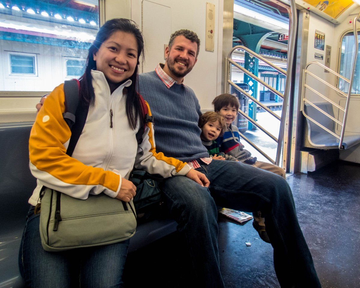 family smiling on a subway - New York