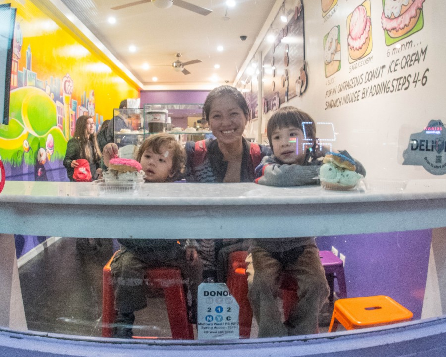 A mother and two young boys smile through the window of a bakery