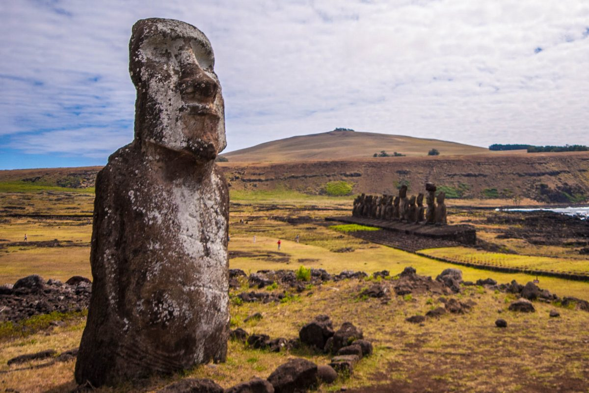 A moai stands overlooking an ahu with 15 moai sculptures on it. In the background is a mountain.