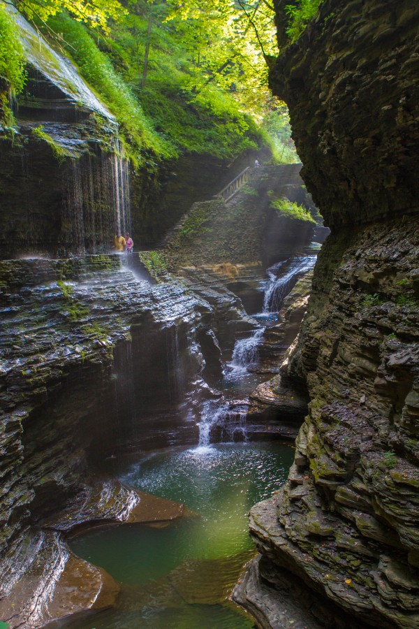 Glen of Pools with rays of sun streaming down onto the gorge and rock bridge in the background.