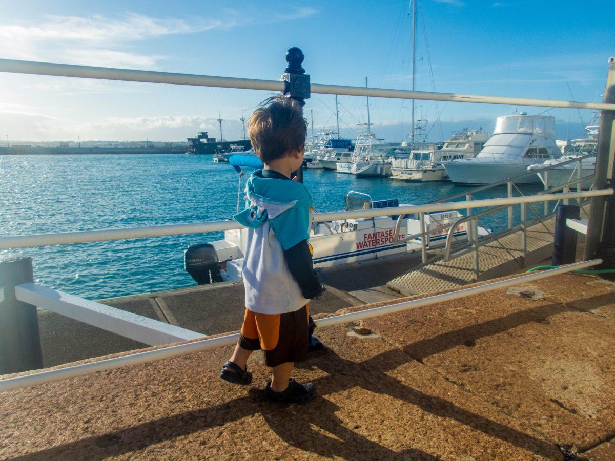Toddler wearing swim gear walks along a boat pier - Boating in Bermuda