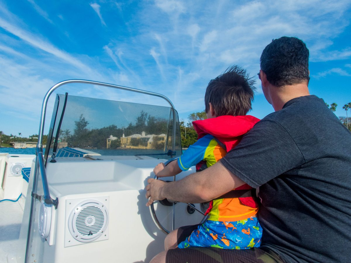 a young boy sits on his Dads lap as they boat through a Bermudian harbour - Boating in Bermuda