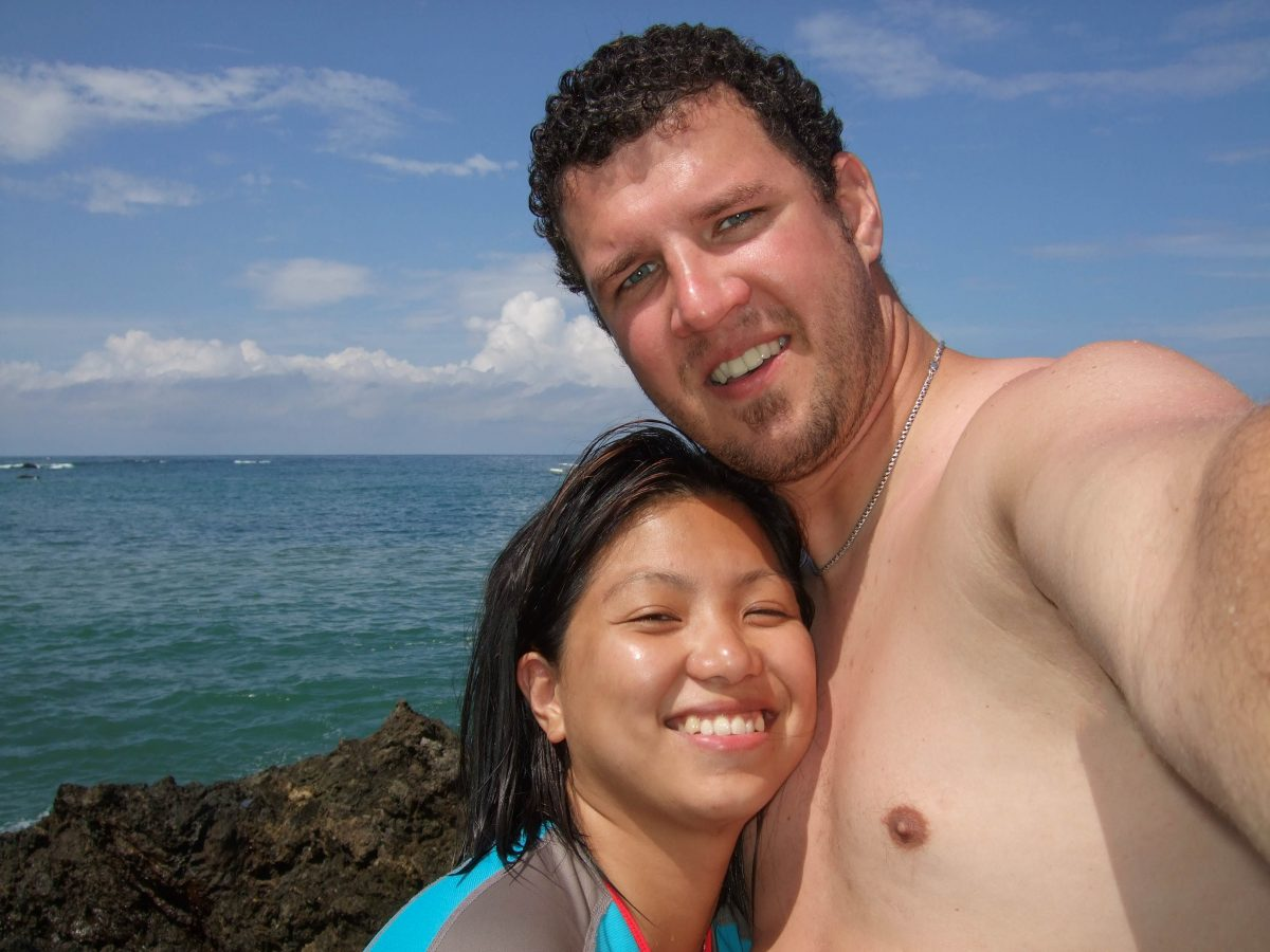 A young man and woman hug and smile at the camera - finding paradise in the osa peninsula