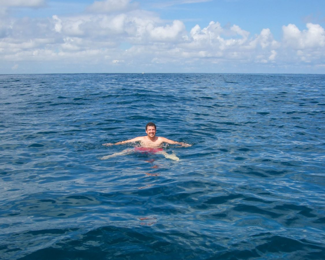 A man smiles while swimming in the middle of the Caribbean sea - finding paradise in the osa peninsula