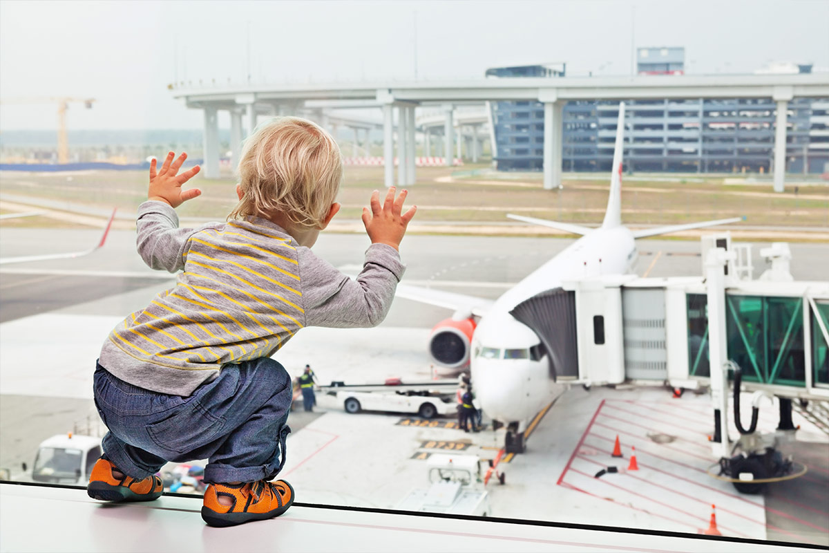 Toddler looking out the window of an airport as a plane is loaded in the background
