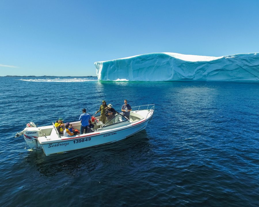 A small boat of tourists photographs a large iceberg in Twillingate, Newfoundland - Icebergs in Twillingate