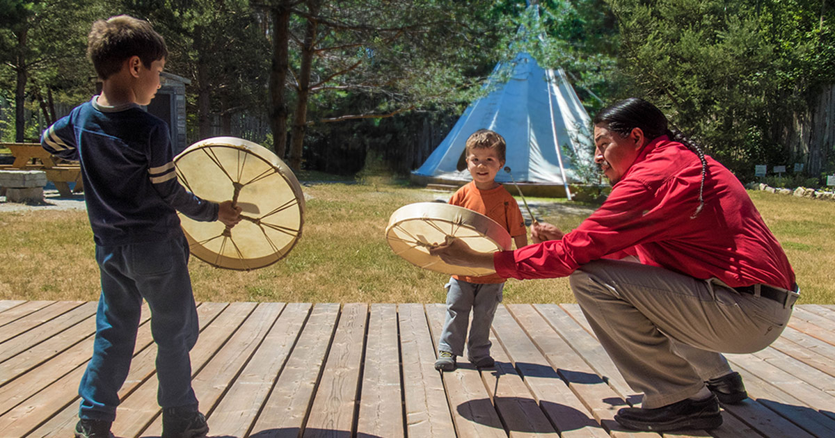 Two young boys get a native drum lesson at a First Nations experience on Manitoulin Island Ontario
