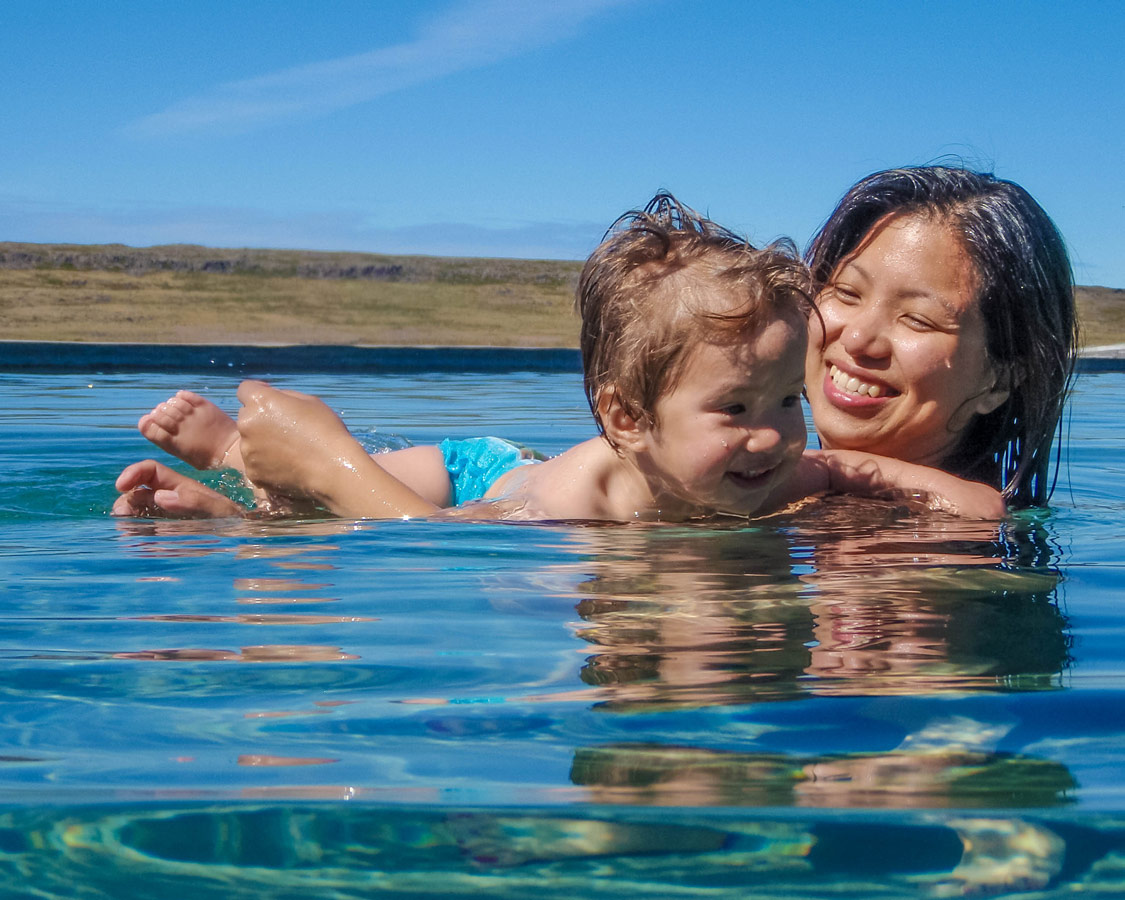 A mother shows her young son some swim moves in a natural pool in Iceland - An Epic 14 Day Iceland Itinerary