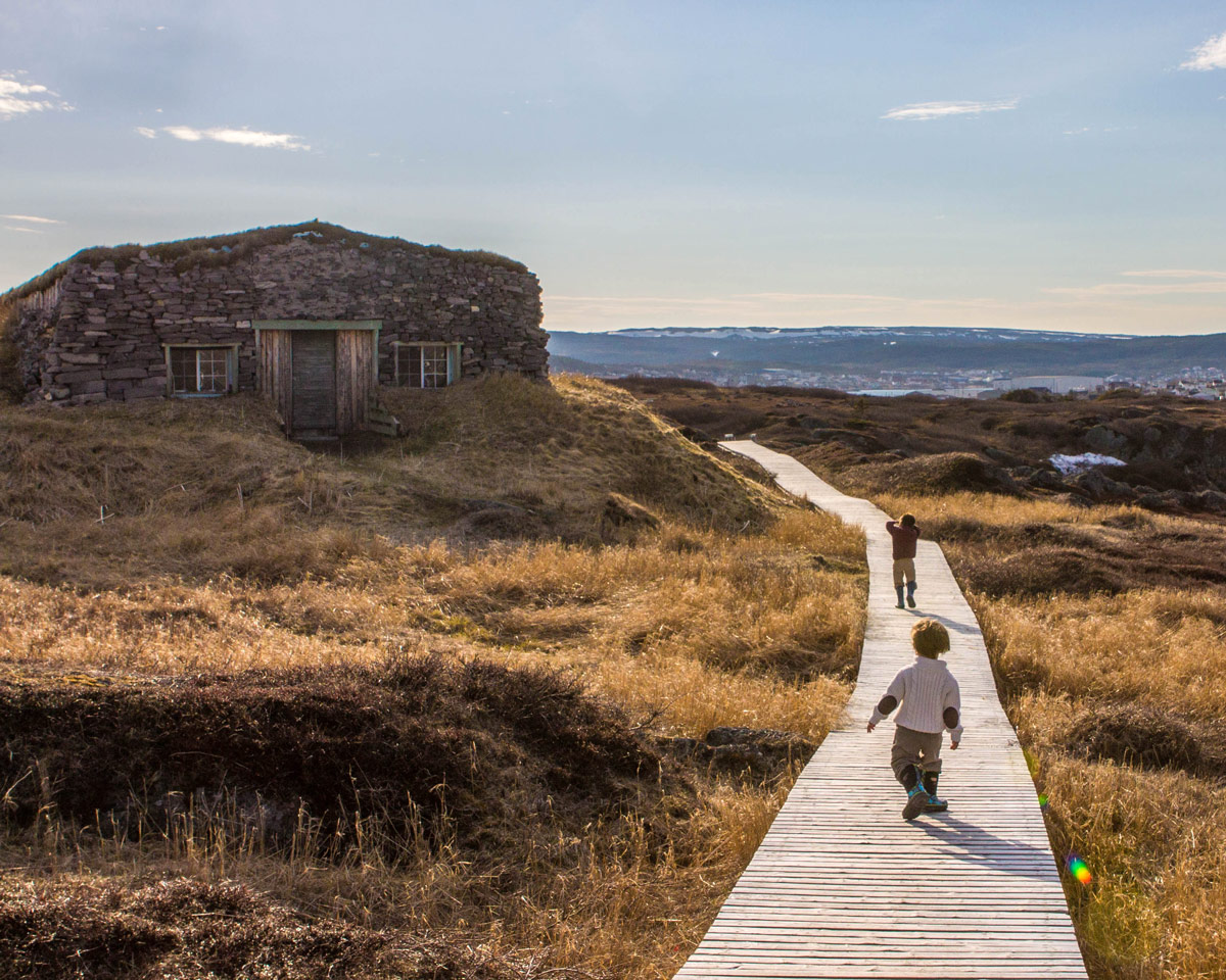Two young boys walk along a boardwalk towards a grass covered stone building - Newfoundland Viking Trail