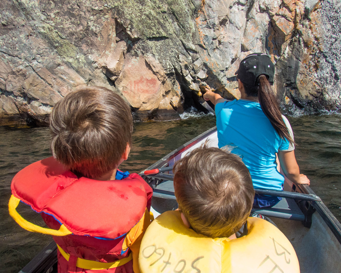 A mother points to a native pictograph from a canoe - Top things to do in Bon Echo Provincial Park