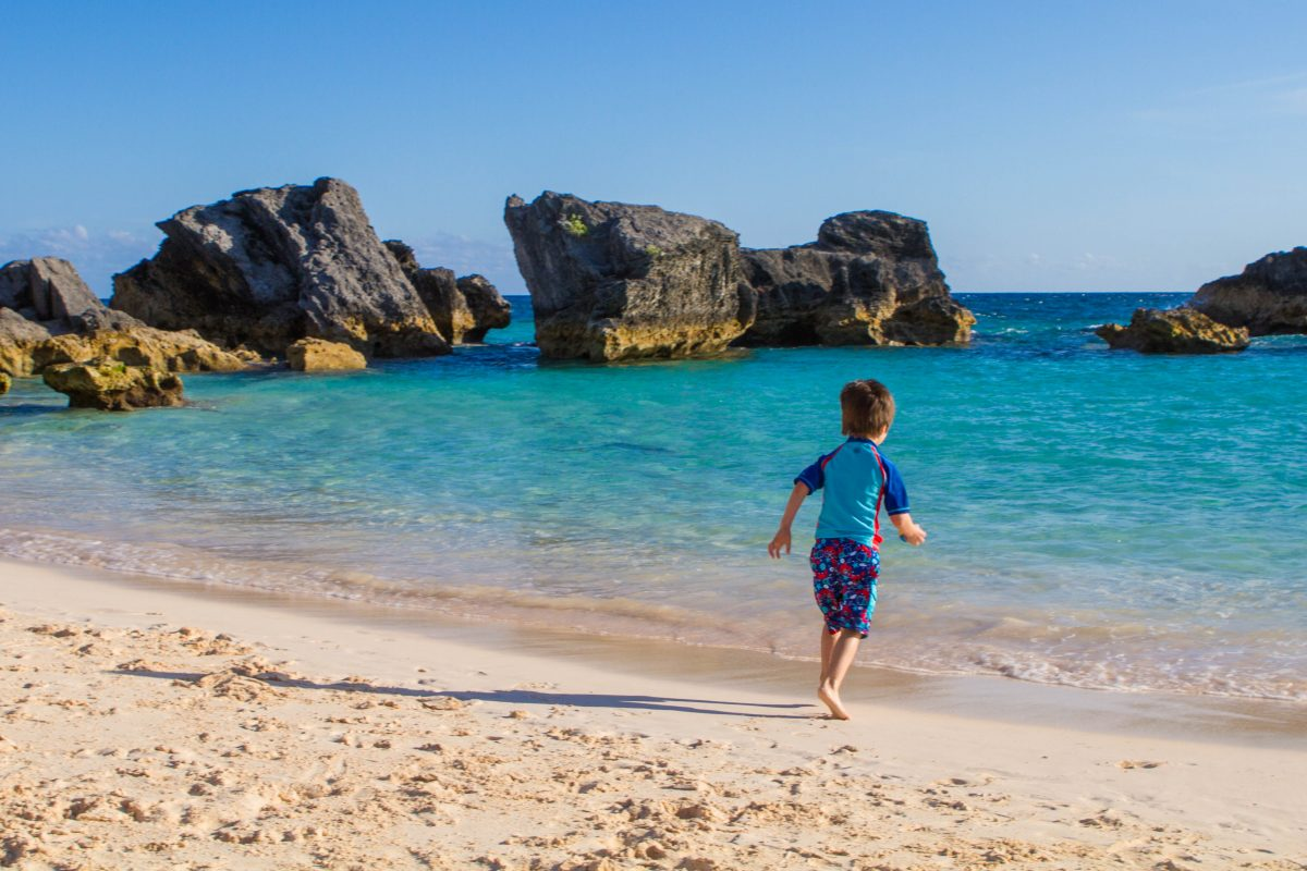 Best Beaches In Bermuda Boy running towards East Whale Beach on our search for the best Bermuda beach.