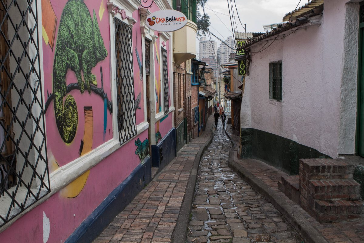 Picture of narrow cobblestone lined street with graffiti art lining one side of the street in La Candelaria.