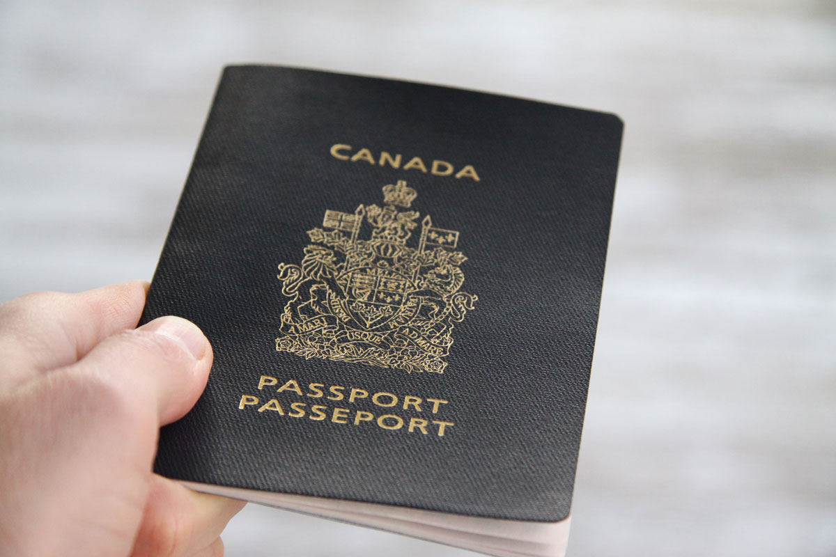 A closeup of a hand holding a Canadian passport - plan international family vacations
