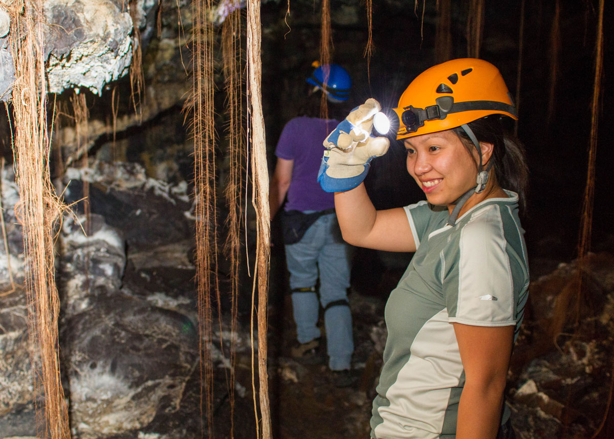 A woman wearing a hardhat and headlamp looks at vegetation in a lava tube - caves you can visit with kids