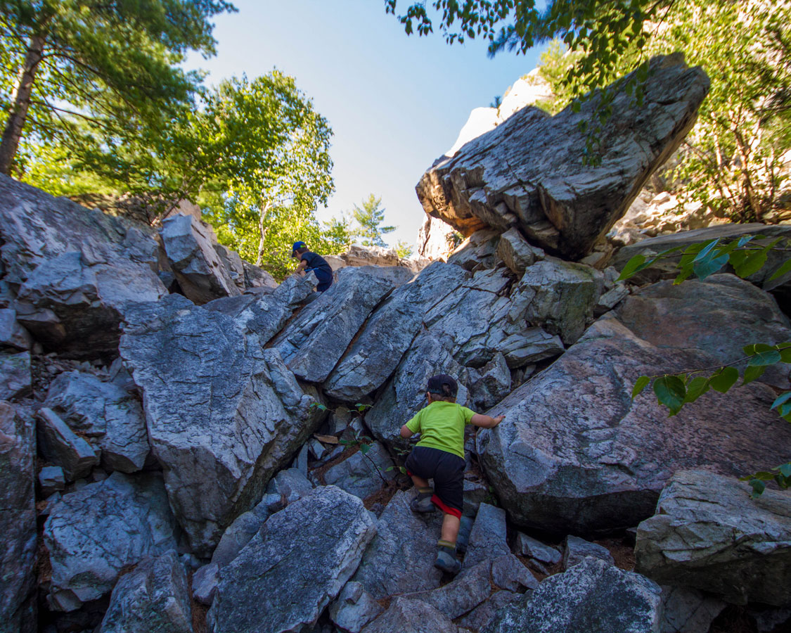 A toddler climbs a large rock fall in Killarney Provincial Park - Hiking the Crack in Killarney with Kids