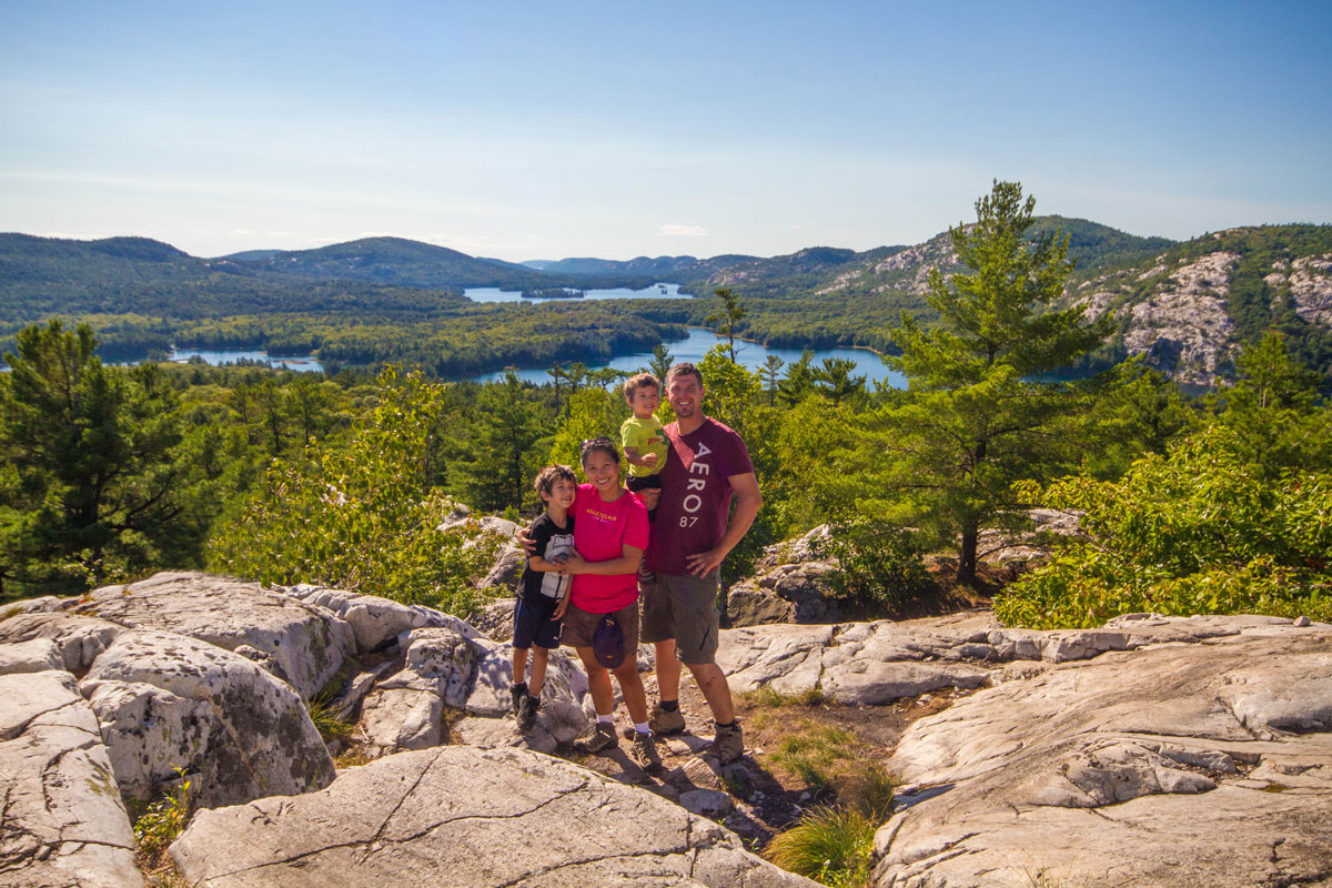 A young family smiles and poses at a viewpoint over lakes and forests - Hiking the Crack in Killarney with Kids