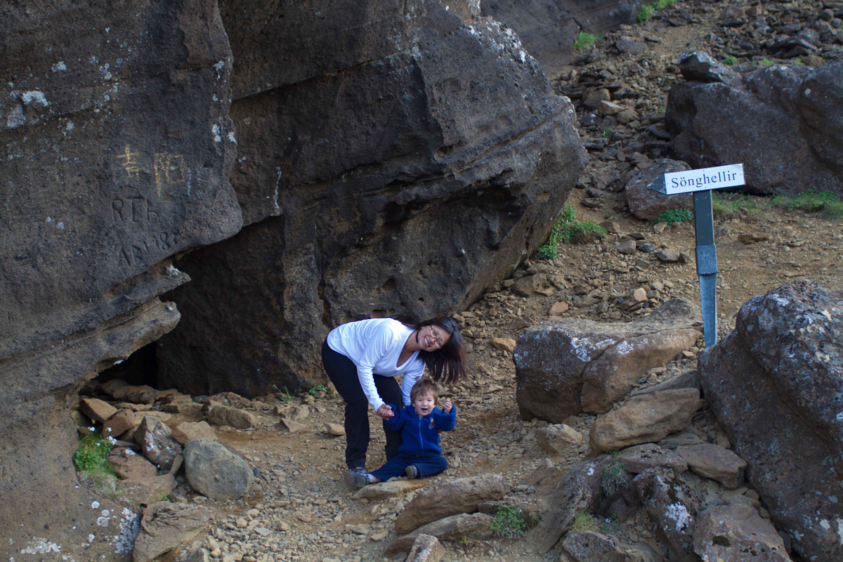 A woman and her young son smile outside a small cave in Iceland - Caves you can visit with kids