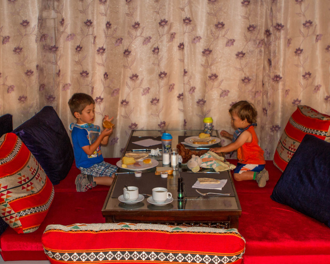 two young boys eat breakfast in a bedouin tent in the Wadi Rum Desert of Jordan - plan international family vacations