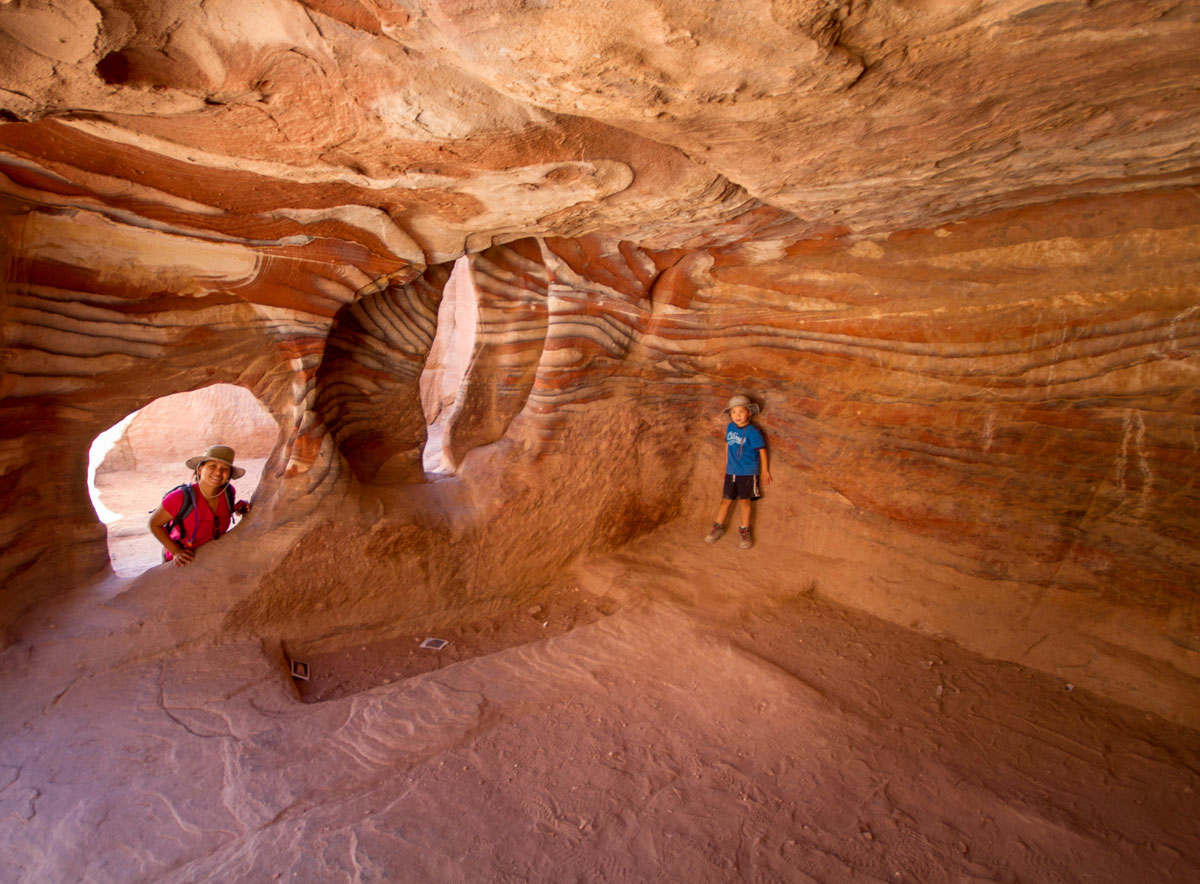 A young boy smiles inside a cave in Petra Jordan while his mother watches - caves you can visit with kids