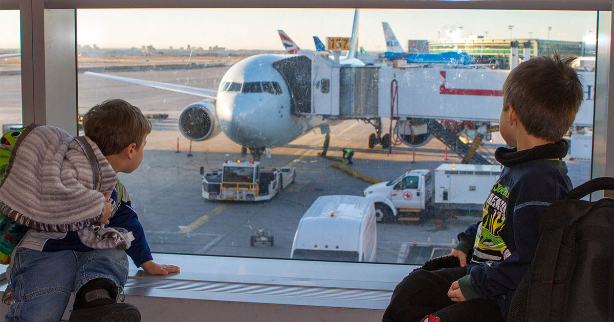 Two young boys watch planes out of an airport window - plan an international family vacation