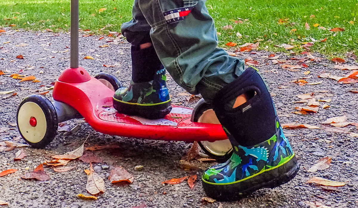 Close up of boots and scooter of a young boy - Bogs kids winter snow boots