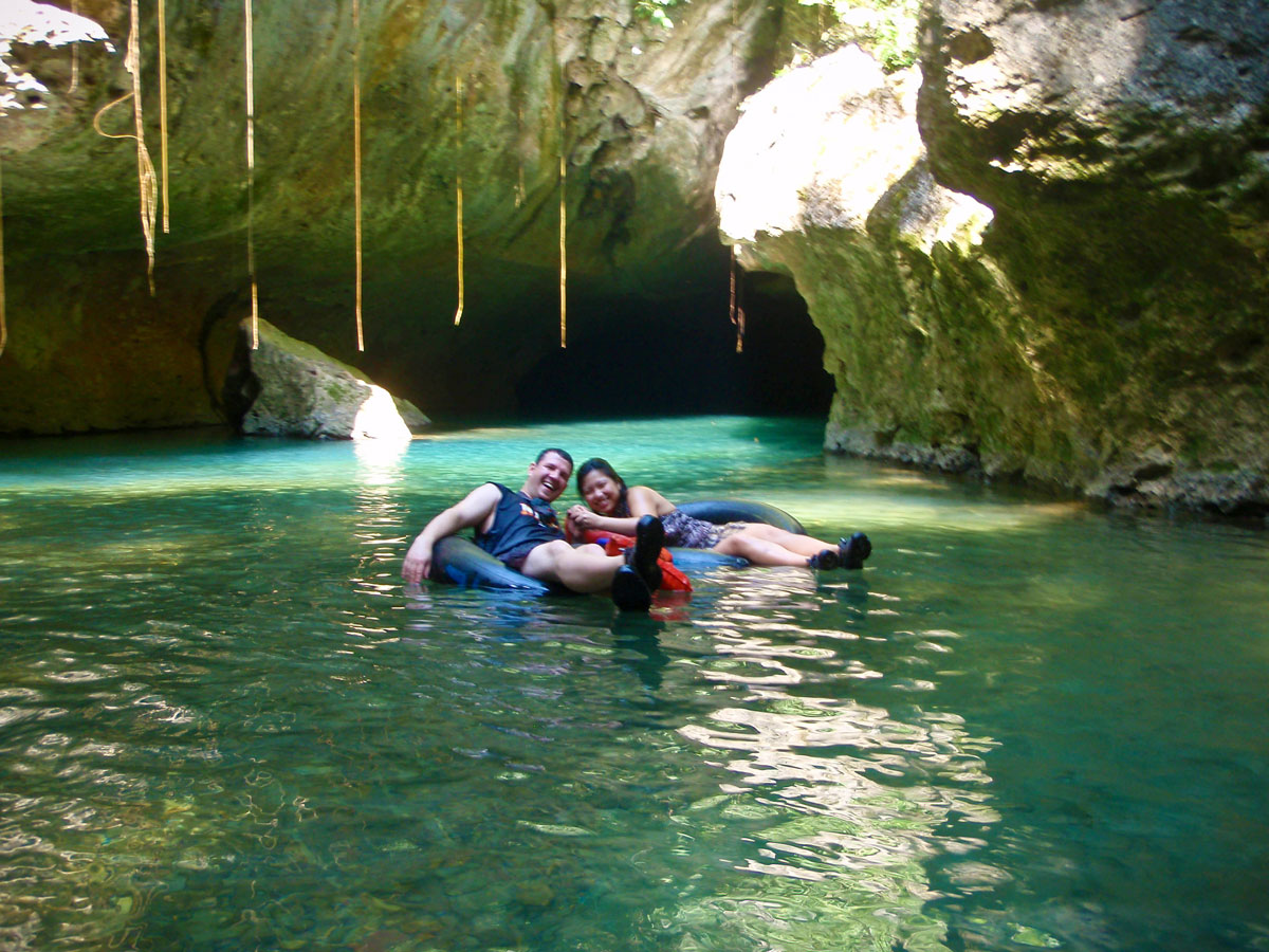 Man and woman cave tubing in Belize's Nohoch Che'en Caves Branch Reserve which is one of the must do activities in Belize.