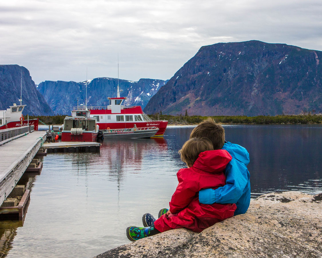 Two young boys wearing rain outfits hug in front of a marina at Western Brook Pond in Gros Morne National Park