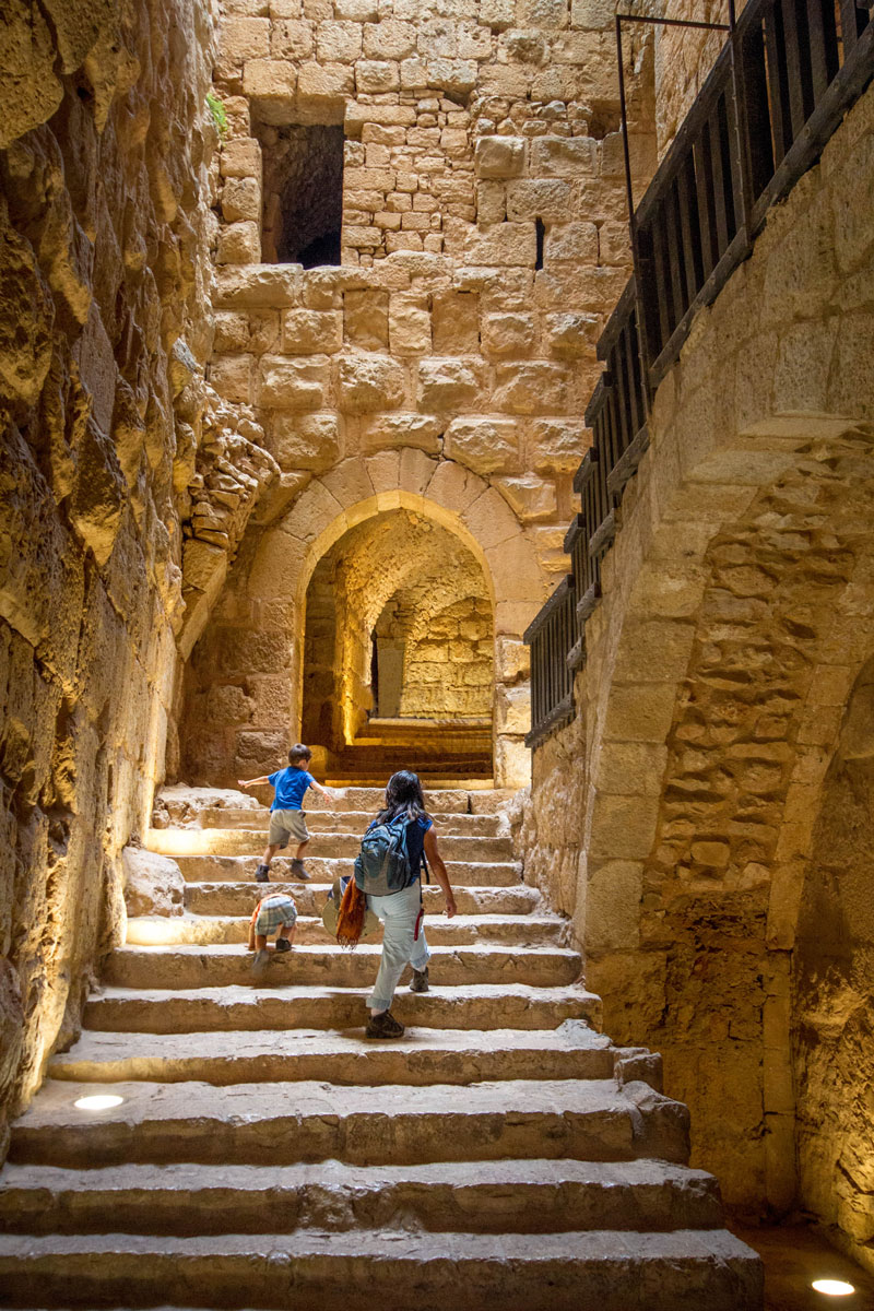 A woman and two young boys climb the stairs of a castle in Jordan