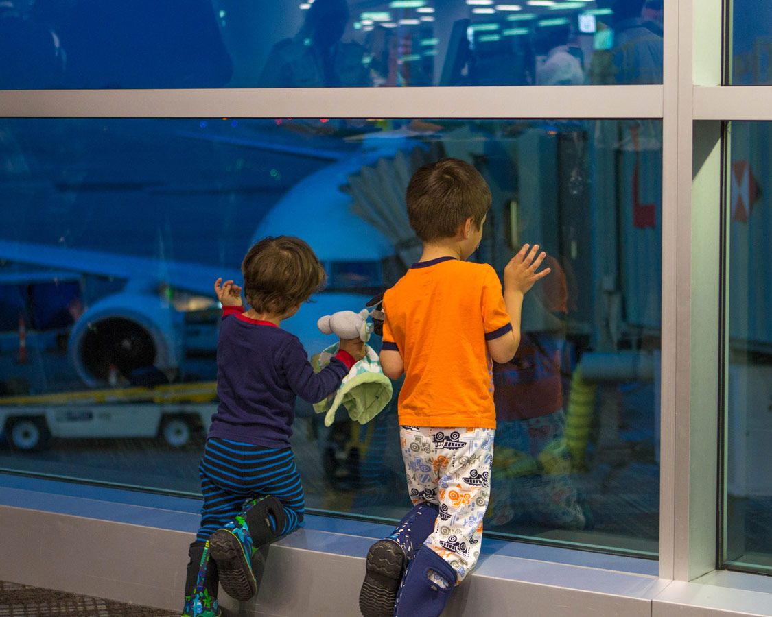 Two young boys stare out the window at an airport