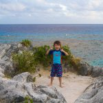 A young boy flexes his muscles on a patch of sand at the top of a cliff overlooking the ocean in Bermuda