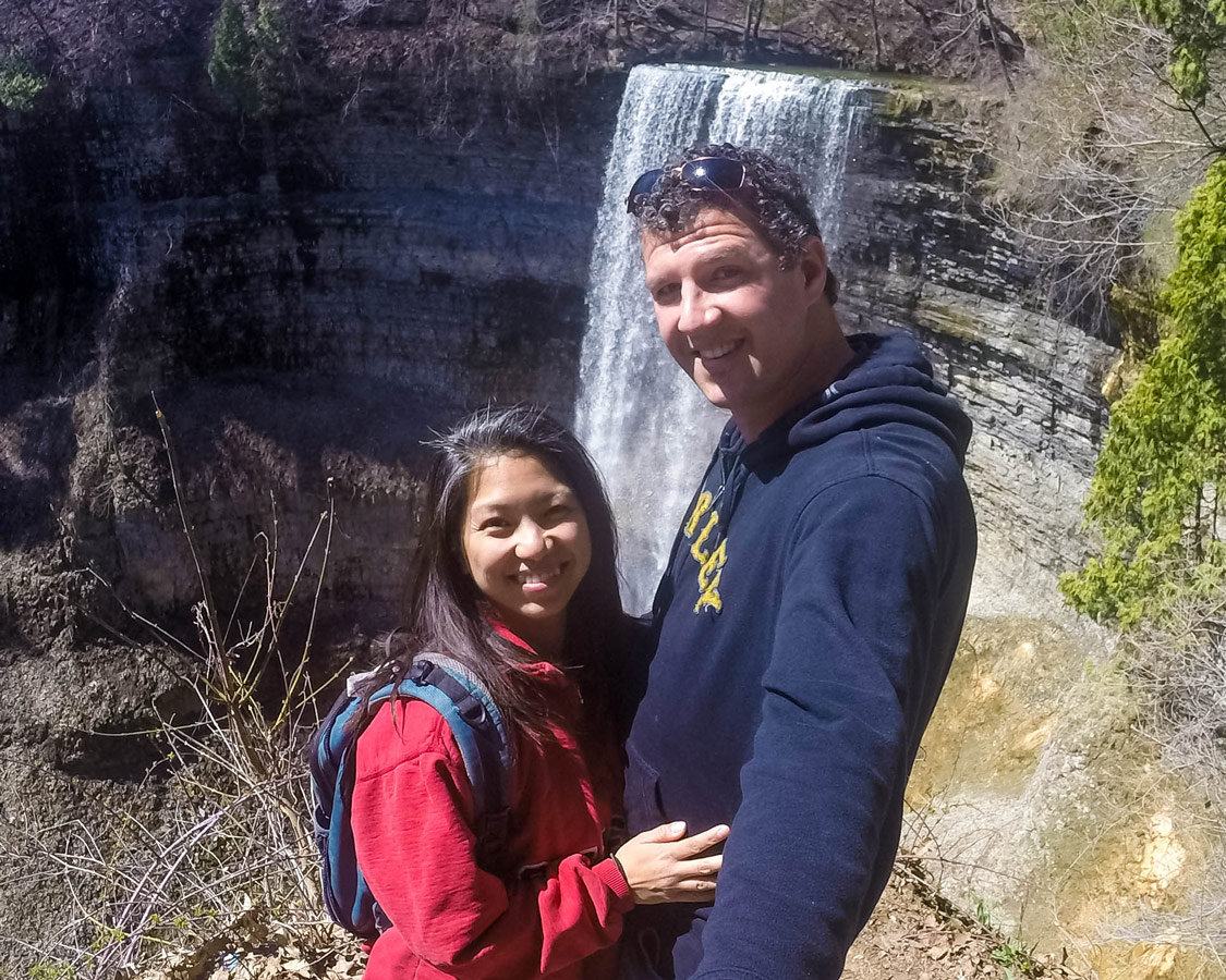 A young couple poses for a selfie in front of a waterfall in Hamilton, Ontario