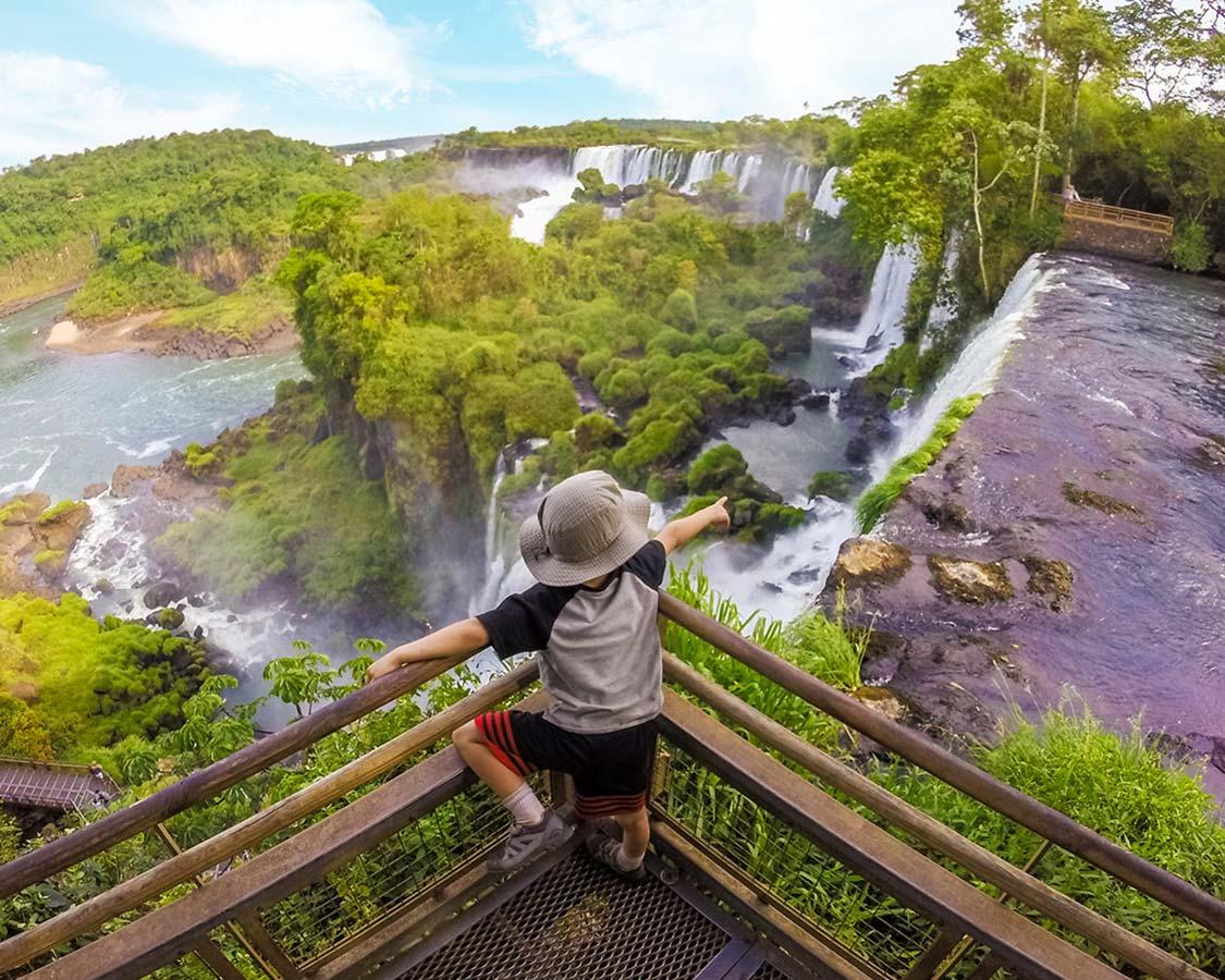 Boy pointing at Iguazu Falls Argentina from boardwalk