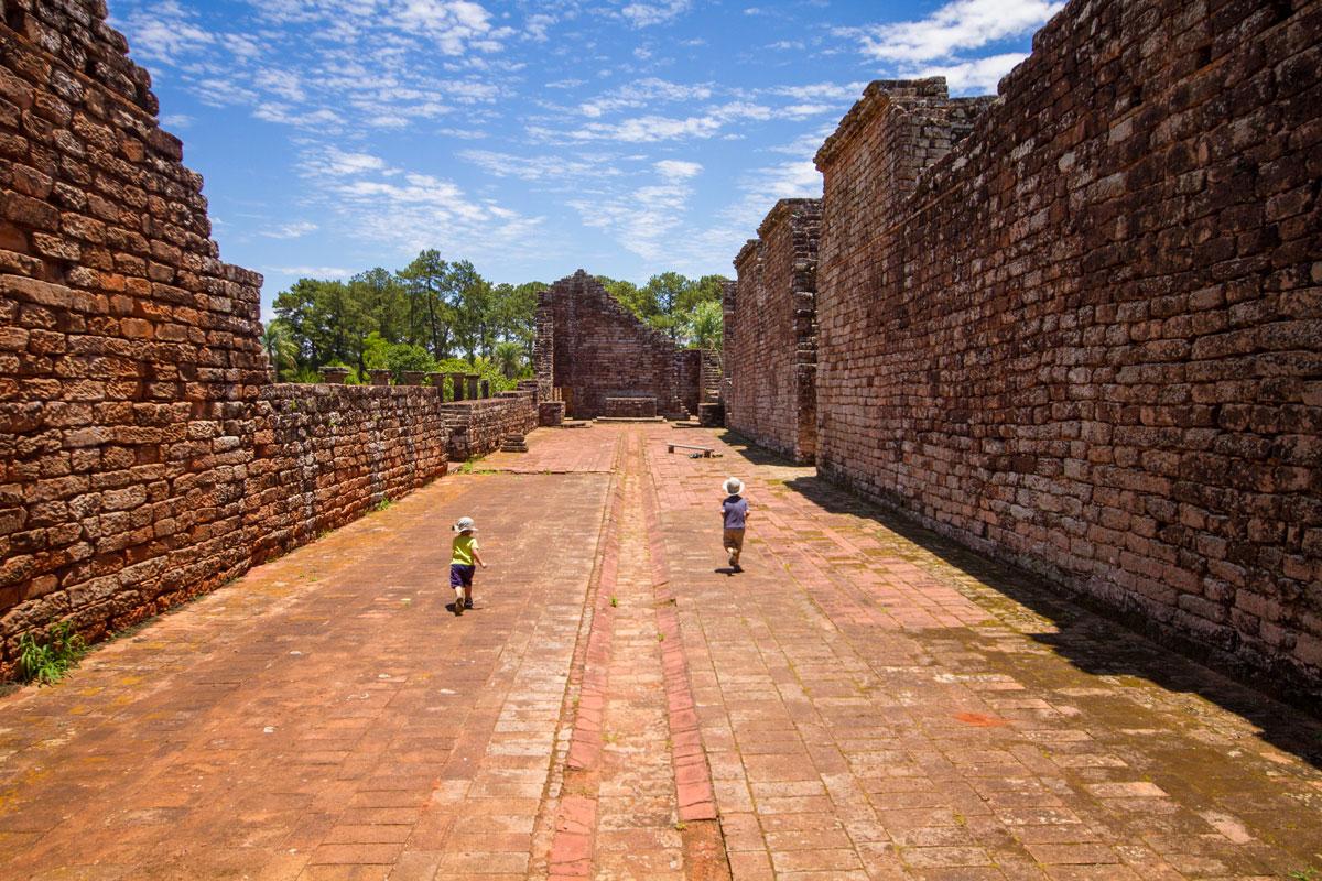 Boys run along the ruins of a church in la Santisima Trinidad de la Parana Jesuit ruins in Paraguay