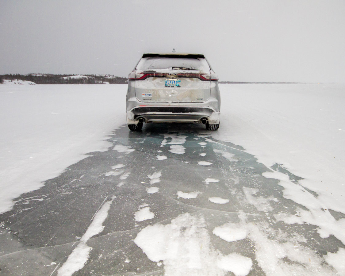 Car driving on Dettah ice road in one of our top winter activities to do in Yellowknife with kids.